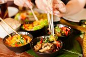 image of sate  - Young people eating in a Thai restaurant - JPG