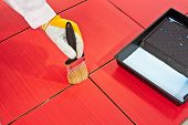 picture of grout  - Hand in yellow glove painting with black brush primer on grout of red tiles resistant - JPG