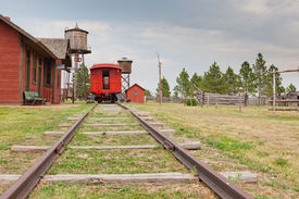 foto of caboose  - Looking down the tracks at a bright red caboose of a train pulled in to an old west style station with a water tower and telegraph wires - JPG