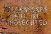 An old weathered painted Trespassers sign