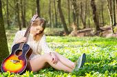 Portrait Of A Beautiful Blond Woman Relaxing With Guitar Under Tree