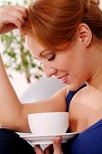 Middleaged happy woman enjoy her morning cup of tea at home