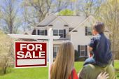 image of yard sale  - Curious Family Facing For Sale Real Estate Sign and Beautiful New House - JPG