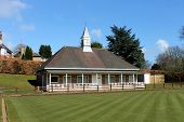 Scenic view of English bowling green and pavilion with clock tower.