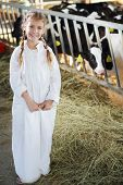 Cute girl in white robe with hay stands near stall with small calves at large farm.