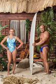 Muscular man with a surfboard and beautiful girl on a beach with palms
