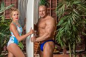 Muscular man in trunks and beautiful girl in swimsuit with a surfboard near the house with palms