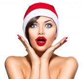 Christmas Woman. Beauty Model Girl in Santa Hat isolated on White Background. Funny Laughing Surpris