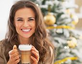 Portrait Of Smiling Young Woman With Latte Macchiato Near Christ