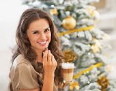 Happy Young Woman Eating Candy With Latte Macchiato Near Christmas Tree