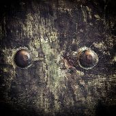 stock photo of stelles  - Closeup of grunge black metal plate with rivets and screws as background or texture - JPG