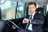 stock photo of car ride  - Young successful businessman riding in the car - JPG