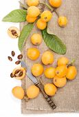 picture of loquat  - loquats with leaves on a linen napkin on a white background - JPG
