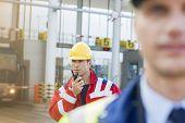 stock photo of shipyard  - Male worker using walkie - JPG