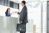 pic of receptionist  - Businessman receiving document from receptionist in office - JPG