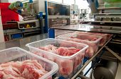 stock photo of slaughterhouse  - Workers taking the lumps of meat in a container - JPG