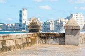 stock photo of malecon  - The famous malecon seawall in Havana vith a view of the city skyline - JPG