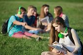 foto of peer-pressure  - Sad female teenager sitting outdoors with books  - JPG