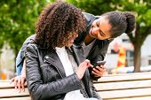 stock photo of bff  - Two north African teen friends reading and writing text message on mobile phone in park   - JPG