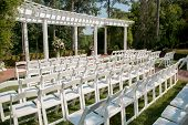 stock photo of pergola  - White chairs lined up before an outdoor summer wedding - JPG