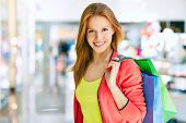 stock photo of charming  - Charming customer with shopping bags looking at camera - JPG
