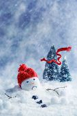 pic of sad christmas  - Snowman melting with scarf blowing away into Christmas trees - JPG