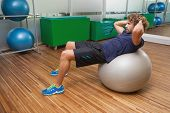stock photo of crunch  - Side view of handsome young man doing abdominal crunches on fitness ball in gym - JPG