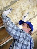 stock photo of attic  - Worker thermally insulating a house attic using mineral wool - JPG