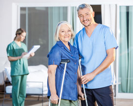 stock photo of nursing  - Portrait of happy male caretaker and disabled senior woman with female nurse in background at nursing home yard - JPG