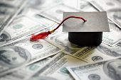 pic of education  - Graduation mortar board cap on one hundred dollar bills concept for the cost of a college and university education - JPG