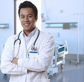 stock photo of coat  - Portrait of happy asian doctor in lab coat standing at hospital room - JPG