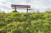 stock photo of dike  - The of the deck is covered with grass and on top of the dike is an empty wooden bench - JPG