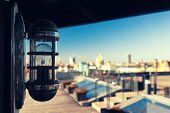 picture of roof-light  - Light bulb in a summer cafe on the roof over modern city background - JPG