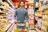 stock photo of supermarket  - Handsome man shopping in a supermarket - JPG