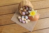 stock photo of easter candy  - Pastel candy Easter eggs in a wicker basket with a daffodil - JPG