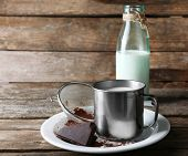 image of bittersweet  - Metal mug and glass bottle of milk with chocolate chunks and strainer of cocoa on plate and rustic wooden planks background - JPG