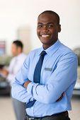 stock photo of showrooms  - portrait of african vehicle salesman in showroom - JPG