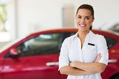 stock photo of showrooms  - young female car sales consultant working in showroom - JPG