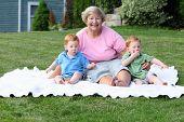 stock photo of nic  - Happy grandmother holding twin boys - JPG