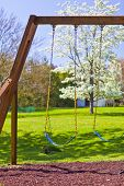 pic of swingset  - Wooden playset with swings on summers day - JPG