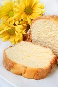 stock photo of pound cake  - Slice of pound cake on a white plate and yellow daisies - JPG