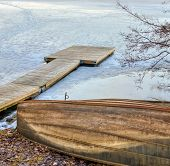 picture of pier a lake  - Old wooden rowboat and a pier in the frozen lake - JPG