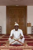 stock photo of islamic religious holy book  - Black African Muslim Man Reading Holy Islamic Book Koran - JPG