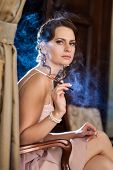 foto of smoking woman  - Pretty woman is sitting on the chair and smoking cigarette - JPG
