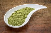 stock photo of teardrop  - moringa leaf powder in a teardrop shaped bowl against rustic wood - JPG