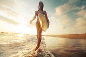 stock photo of board-walk  - Surfer girl walking with the surf board on the beach - JPG