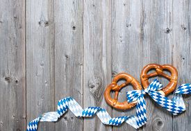 image of pretzels  - Bavarian pretzels with ribbon on wooden board as a background for Oktoberfest - JPG