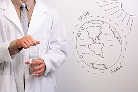 stock photo of ozone layer  - Man in a white lab coat opening a bottle of water while standing next to a drawing of the ozone layer - JPG