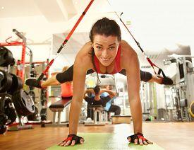 stock photo of suspension  - Happy woman enjoying hard suspension training in gym - JPG
