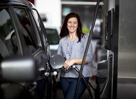 stock photo of petrol  - Pretty woman filling her car with petrol at gas statiion - JPG